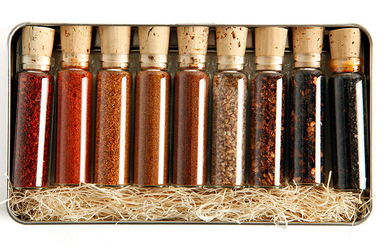 9 glass vials of hot pepper powders and spices, sealed with a cork. In a metal tin with straw packing.