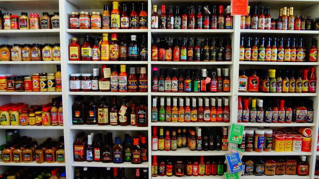 Wall of hot sauces on shelves at a shop