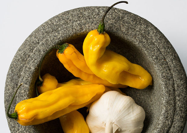 Yellow Madame Jeanette chilli peppers in a granite mortar with a clove of garlic